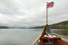 Britische Markierungsfahne auf Bootswekzeugspritze auf See, bewölkter Tag Stockfotografie