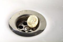 BRITISCHE Pfund-Münze im silbernen Wannen-Abfluss Stockfotos