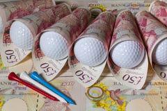 Britische Pfunde und Golfbälle Stockbilder