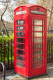 Britische TelekommunikationsTelefonzelle nahe einem Park in London Stockfotografie