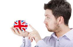 Britischer Mann, der mit piggy Querneigung spielt lizenzfreie stockbilder