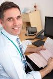 Britischer Mann-GP, der am Schreibtisch sitzt Stockfotografie