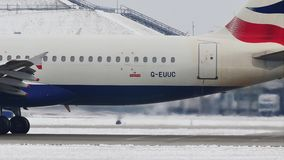 British Airways Airbus A320-200 G-EUUC doing taxi in Munich Airport, snow. American Airlines doing taxi in Munich Airport, snow on runways stock footage