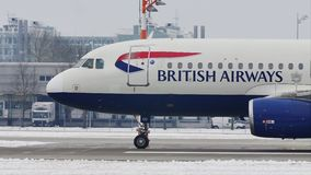 British Airways Airbus A320-200 taxiing on Munich Airport, snow. British Airways doing taxi on snow in Munich Airport, MUC, Germany stock footage