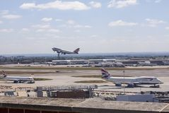 British Airways aircraft at Heathrow Airport. A British Airways Boeing 747 taking off at Heathrow in front of Terminal 4 whilst another British Airways 747 and a stock photos