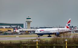 A British Airways plane taxis after landing at London Gatwick Airport, with the air traffic control tower in the background. GATWICK AIRPORT, ENGLAND, UK royalty free stock photo