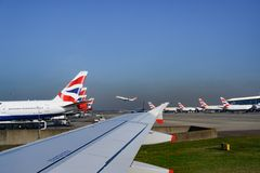 British Airways planes in line on ground in Heathrow Airport. British Airways aircrafts with Union Jack on tail. royalty free stock photo