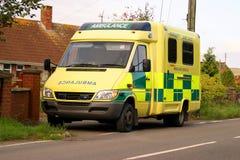 British Ambulance. Bright yellow British Ambulance parked beside the road Stock Image
