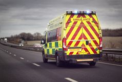 Ambulance emergency on motorway road. British ambulance responding to an emergency in hazardous bad weather driving conditions on a UK motorway royalty free stock photos