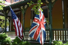 British and American flags in from of Victorian house. British and American flags on display in yard of Victorian house in Cape May, New Jersey Royalty Free Stock Photography