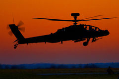Apache Sunset. A British Army AH-64 Apache helicopter comes in to take fuel in the late eveneing light royalty free stock photo