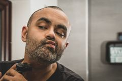 British Asian man, trimming his stubble or beard in front of the mirror. royalty free stock photo