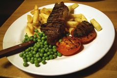 British bar meal of beefsteak, pees, tomato, and chips Royalty Free Stock Images