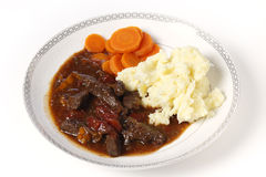 British beef stew. British beef and tomato casserole, served with mashed potatoes and boiled carrots Stock Photos