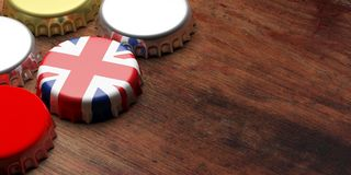 English beers. Beer cap with UK flag on wooden background, copy space. 3d illustration. British beers. Beer cap with UK flag on wooden background, copy space. 3d Royalty Free Stock Photo