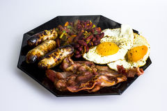 Traditional British breakfast. British breakfast served the traditional way with crispy bacon, fried eggs, sausages and red beans Stock Photos
