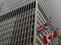 British Canadian Relations. A British Union Jack flag and a Canadian Maple leaf flag fly side by side outside a corporate office building royalty free stock photography