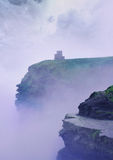 British castle. British mystical atmosphere of the castle in the mist over the precipice Stock Photos