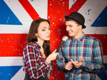 British chat show host. Female British chat show host interviewing a handsome young men in a bowler hat in front of a Union Jack flag painted on the wall Royalty Free Stock Photo