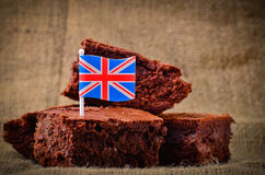 British chocolate brownies. Chocolate brownies on a rustic hessian background with a Union Jack flag Royalty Free Stock Images