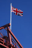 British coal. The union jack flag of Great Britain flying over the winding gear of a coal mine. Slight motion blur on the tip of the flag Royalty Free Stock Photo