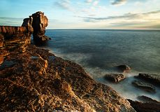 Breath-taking British coastal image showing misty seas crashing against rocks. Royalty Free Stock Photo