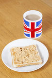 British coffee mug and slice of bread with butter on table Stock Photos