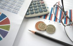 British coins and financial charts. British coins on top of bar chart with calculator and glasses, and pie chart to side with spreadsheet Royalty Free Stock Images