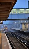 British commuter train pulling into suburban railway station Stock Images