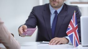 British consular officer giving passport to immigrant, tourist visa approval. Stock footage stock video footage