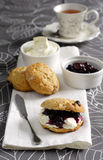 British cream tea. Scones, blueberry jam, clotted cream and a cup of black tea Royalty Free Stock Photo