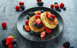 British Crumpets breakfast with blueberries, strawberries, blackberries, raspberries drizzled with icing sugar Royalty Free Stock Photography