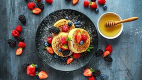 British Crumpets breakfast with blueberries, strawberries, blackberries, raspberries drizzled with icing sugar Royalty Free Stock Photos