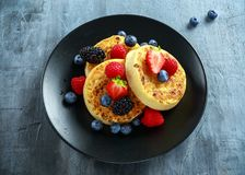 British Crumpets breakfast with blueberries, strawberries, blackberries, raspberries drizzled with icing sugar Stock Photos