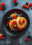 British Crumpets breakfast with blueberries, strawberries, blackberries, raspberries drizzled with icing sugar Stock Images