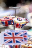 British Cupcakes at Street Party. Close-up of cupcakes with union flag icing and cases. Selective focus with mini Union flags out-of-focus in the foreground Stock Image