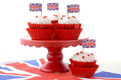 British Cupcakes with Union Jack Flags. Red white and blue theme cupcakes on red cake stand with UK Union Jack flags on white wood table for Queens Birthday and stock photos