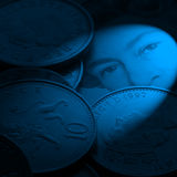 British currency. Close-up if British coins resting on bank note. Blue lighting for effect royalty free stock photography