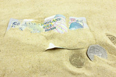 British Currency buried by sand. Stock Photo