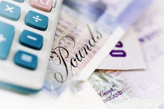 British currency and calculator. Close-up of a Calculator and British Bank notes. Selective focus and soft white vignette Royalty Free Stock Photo