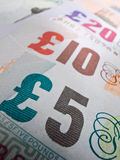British Currency Close-up. Close-up showing British bank notes in a line. Selective focus on the five pounds Royalty Free Stock Photo