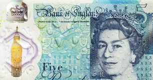 British Currency - Five Pound Note. London, UK: November 12, 2016: Close up of the new polymer five pound note with enhanced counterfeit resilience with water royalty free stock photography
