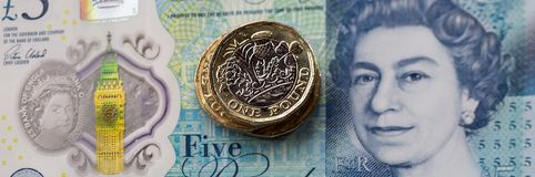 British Currency 2017. London, UK: April 20, 2017: The new bimetallic one pound coin released in March 2017 placed on a new polymer five pound note in a Royalty Free Stock Photos