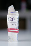 British Currency. A roll of twenty pound notes on a table Royalty Free Stock Images