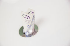 British Currency. Throwing money down the drain Royalty Free Stock Image
