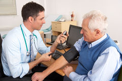 British doctor taking senior man's blood pressure. In doctors office royalty free stock image