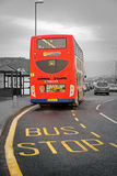 British double decker bus. Photo of a british red double decker bus at yellow bus stop sign lane Stock Photos