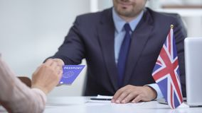 British embassy officer giving passport to immigrant, student visa approval. Stock footage stock video footage
