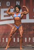 British Female Bodybuilder Shines in Toronto Contest. British female bodybuilder displays an double biceps and sinewy thighs earning her 3rd place in the pro Stock Photos
