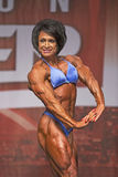 British Female Bodybuilder Shines in Toronto Contest. British female bodybuilder Wendy McCready displays an impressive body, highlighting her sinewy thighs Stock Photos